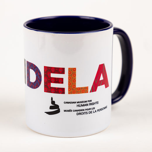 "White mug with blue interior and blue ear that features the text ""DELA"", to spell ""MANDELA""; the icon of the Museum; ""Canadian Museum for Human Rights""; and ""Musée canadien pour les droits de la personne"""