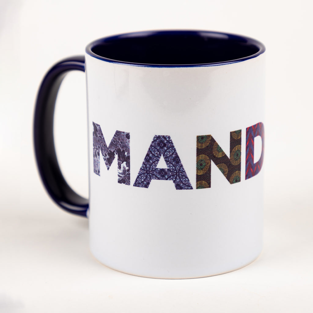 "White mug with blue interior and blue ear. It features the partial text ""MAND"", to spell ""MANDELA"""