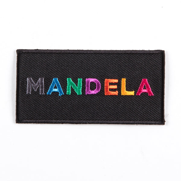 "black patch featuring the text ""MANDELA"" in multi-coloured and multi-patterned capital letters"