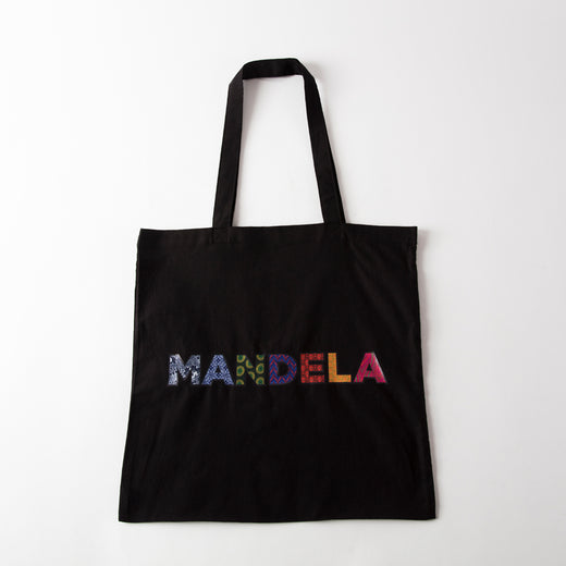 "black tote featuring the text ""MANDELA"" in multi-coloured and multi-patterned capital letters"
