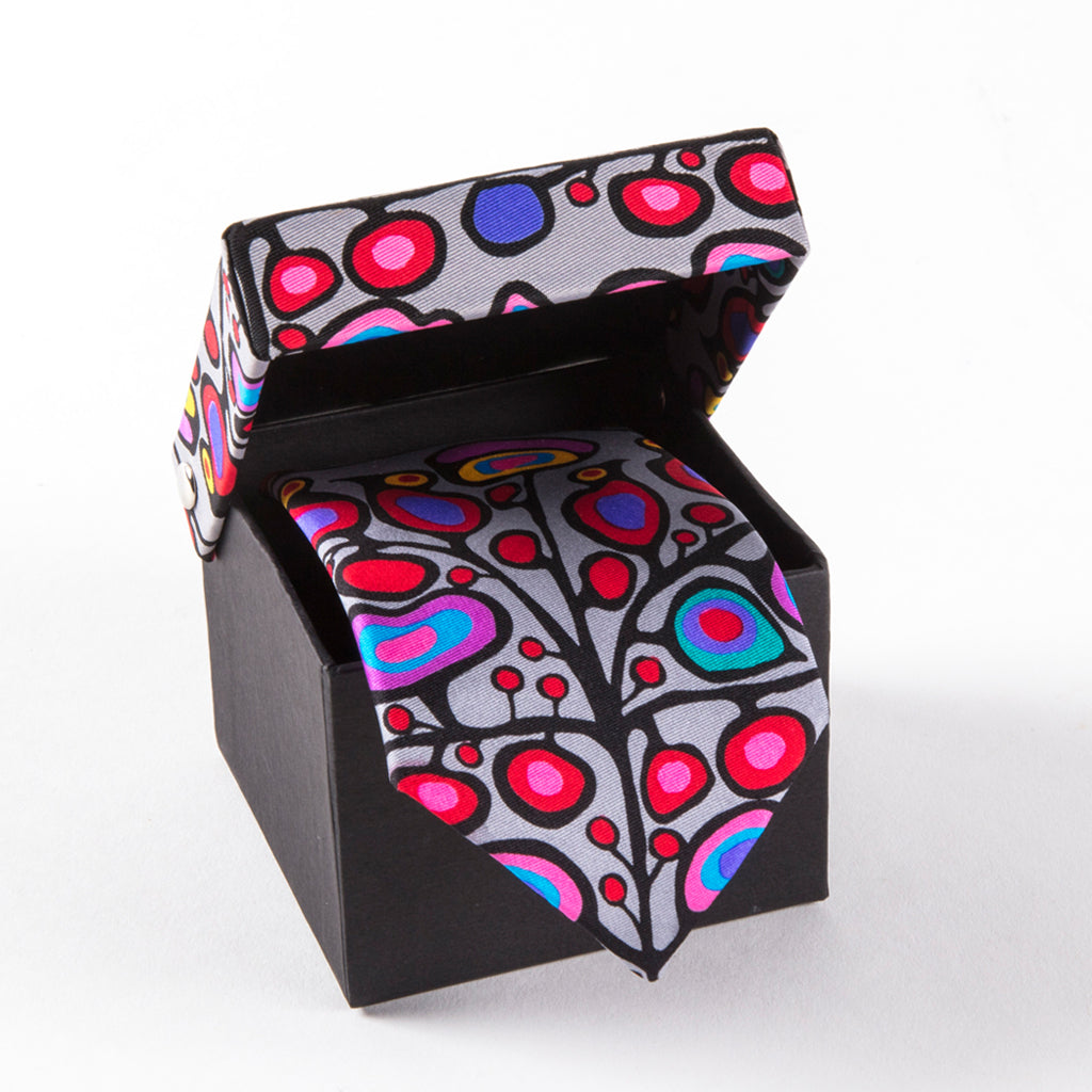 A tie featuring floral artwork and two birds in a gift box featuring an illustration that is similar to the tie's design