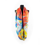 a scarf that features an illustration of a circle, radiant lines and abstract shapes with vibrant colours