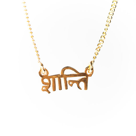 "gold-coloured pendant on a chain; the pendant features the word ""shanti"" in Sanskrit"