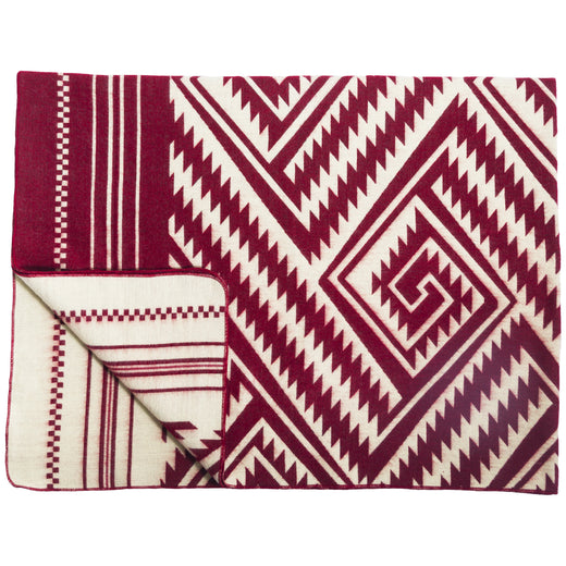 Red and white blanket featuring a geometric spiral design