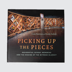 "Book cover with the title ""Picking up the Pieces"", with a photo of the Witness Blanket in the background."