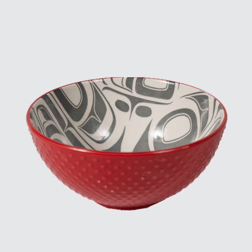 Red textured bowl featuring an inner contemporary Indigenous pattern of eagles.