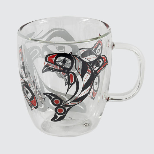 A clear mug with black and red killer whales printed on the outside and a larger shadow killer whale printed on the inside.