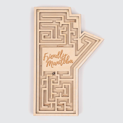 "Wooden labyrinth in the shape of Manitoba, seen from the top. The words ""Friendly Manitoba"" are sculpted in the middle."