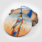 Round ornament featuring art depicting an Indigenous woman. The ornament is leaning on a piece of wood.