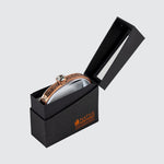 A copper bracelet adorned with a feather motif and an inlaid glass crystal in   an open black gift box and viewed at an angle.