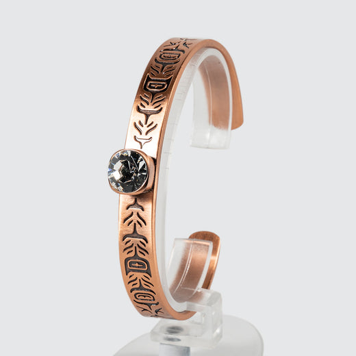 A copper bracelet adorned with a feather motif and   an inlaid glass crystal, viewed at an angle.