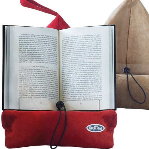 Book support in red with an open book placed on the pillow-like base and resting against the triangular back. A light brown version is in the background.