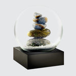 Snow globe on a square black base featuring a buddha at its centre. Viewed at an angle.