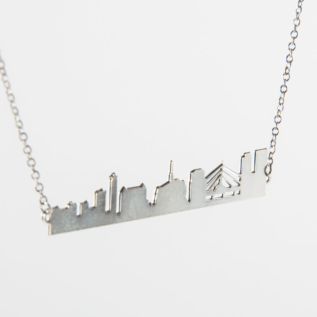 silver-coloured necklace featuring a silhouette of the Winnipeg skyline