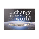 "The front of a pewter cuff featuring the text ""Be the change you wish to see in the world."""