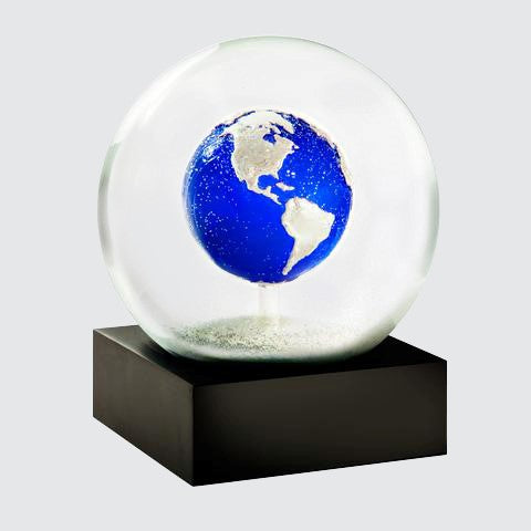 Snow globe on a square black base featuring the planet earth at its centre. Viewed at an angle.