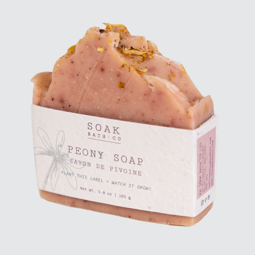 "Salmon coloured soap stood upward with a simple label that says: ""Soak Soap Co."" and ""Peony Soap""."