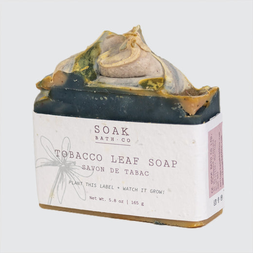 "Soap stood upward with a simple label that says: ""Soak Soap Co."" and ""Tobacco Leaf Soap""."