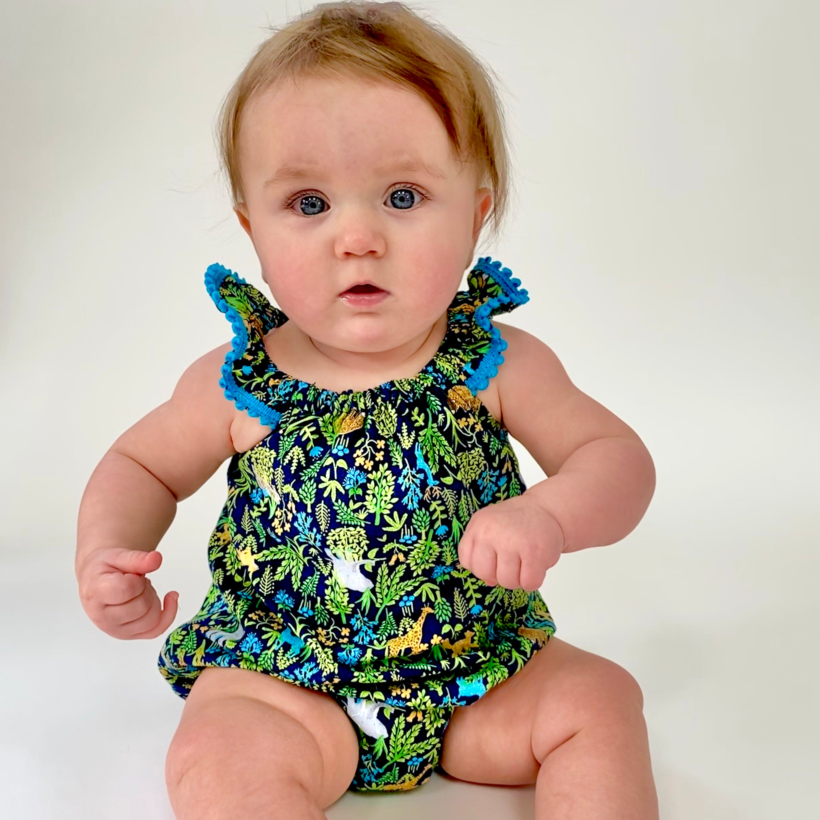 Eddie & Bee Flutter sleeve romper in Navy Animal Jungle print cotton with teal pompom trim