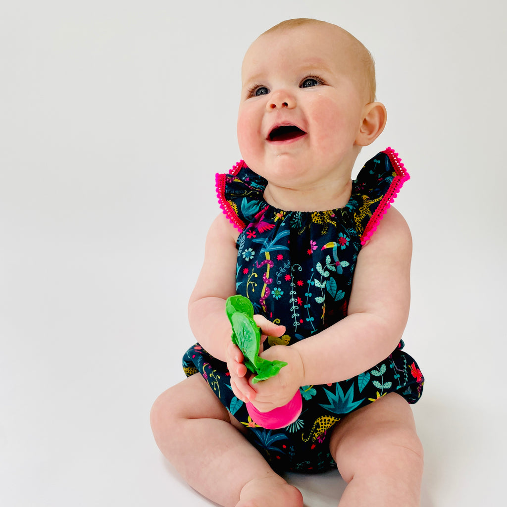 "Flutter sleeve romper in ""Jungle Leopards"" print organic cotton with neon pink pompom trim"