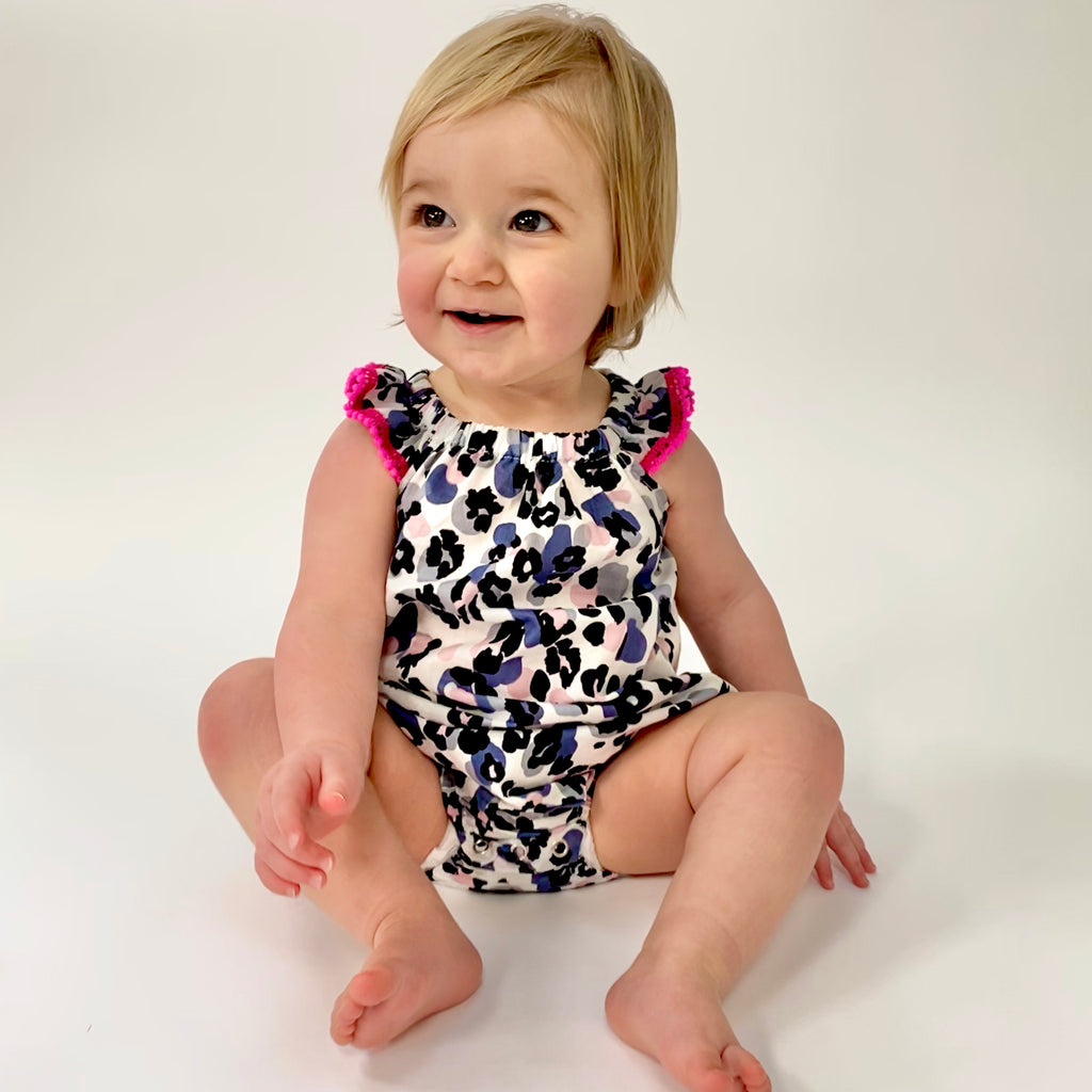 Eddie & Bee Flutter sleeve romper in Cream/blue/pink leopard spot print cotton lawn with hot pink pompom trim