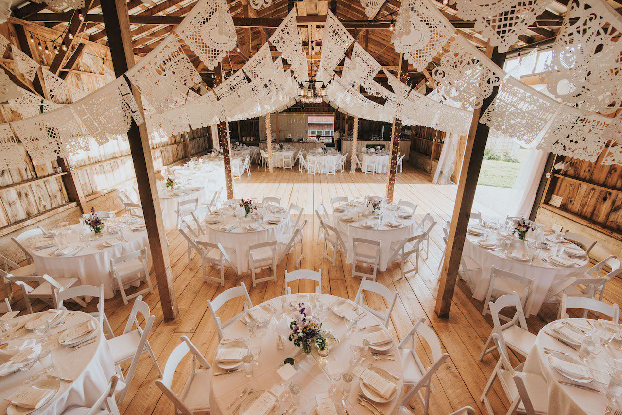 Our client's white personalised wedding papel picado hung in a barn