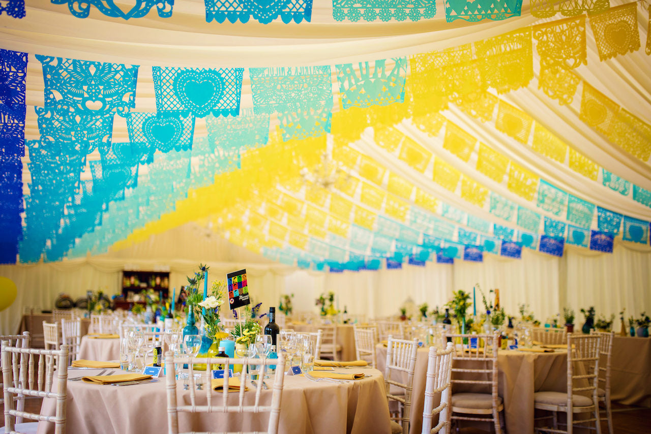 Our client's yellow and blue personalised wedding papel picado hung in a marquee