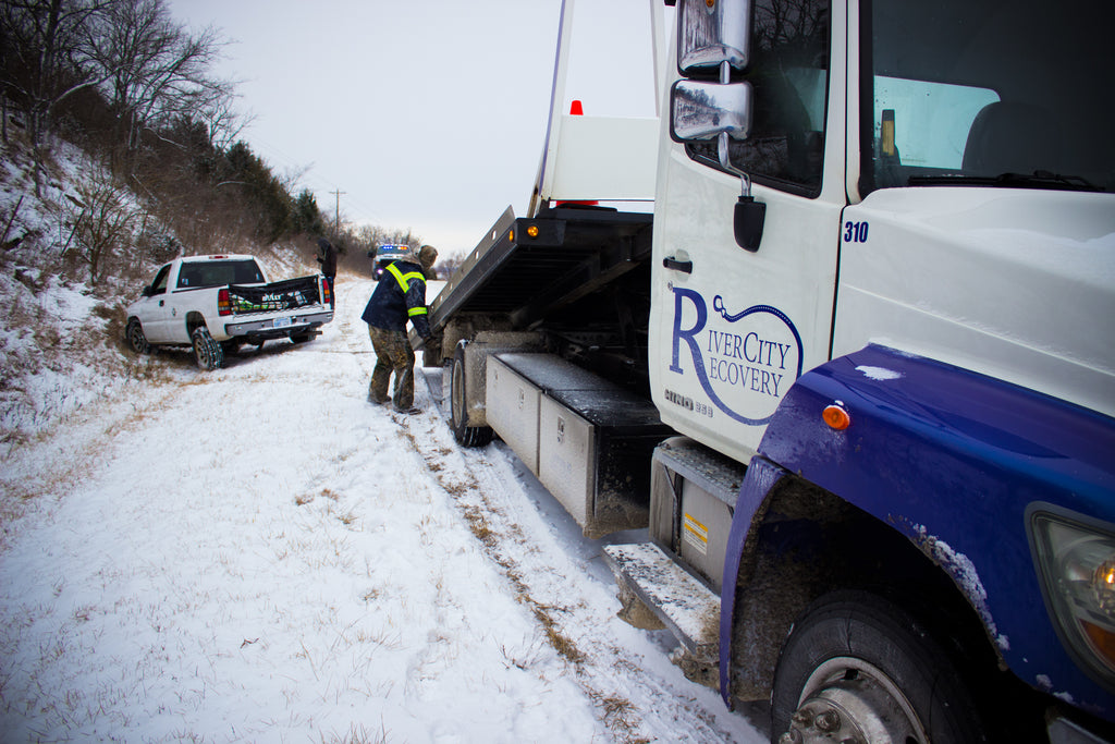 River City Recovery winching a truck out of the ditch on a snowy day in Lawrence, Kansas.