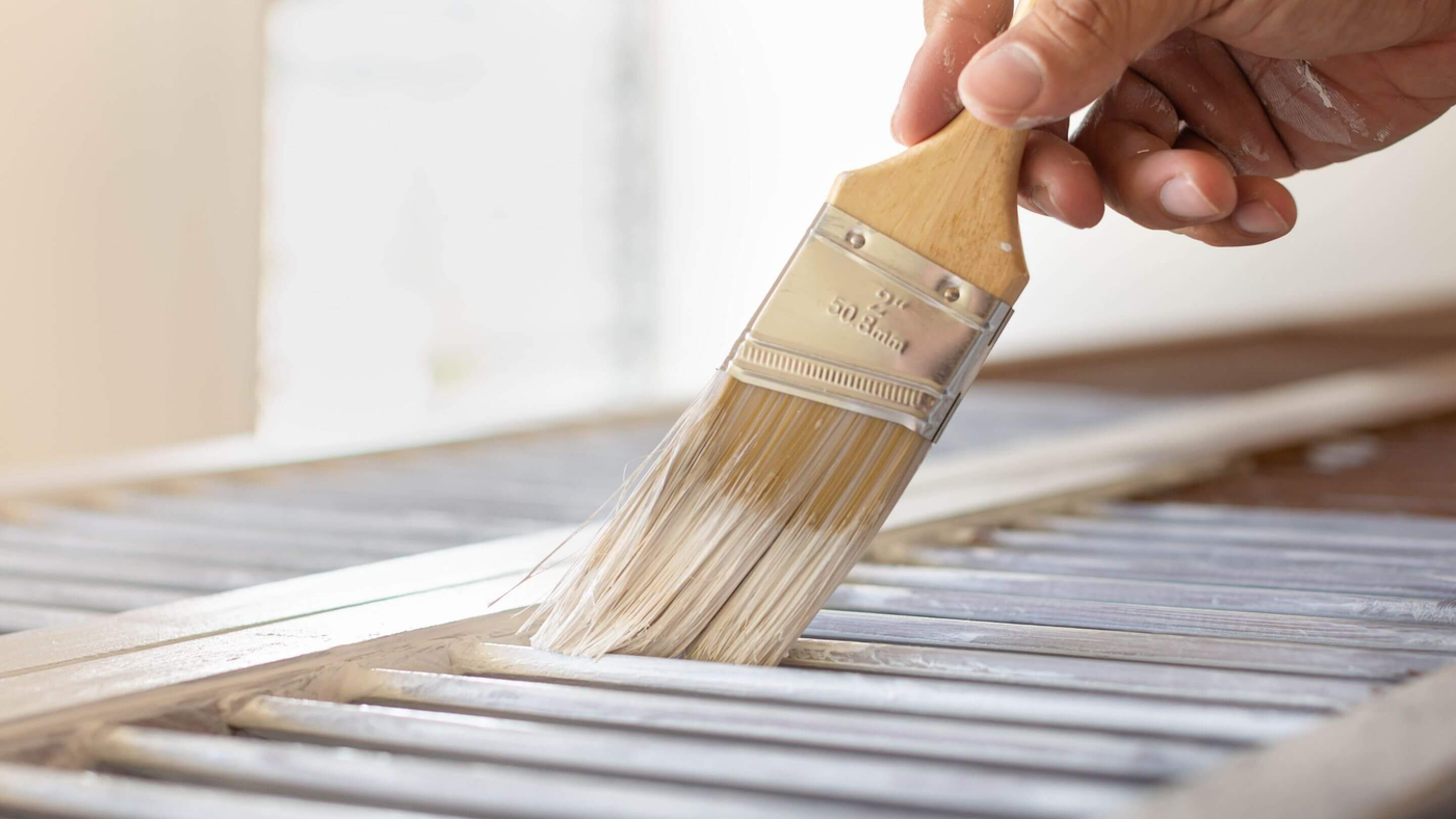 person painting wooden rack with wood grain paint brush