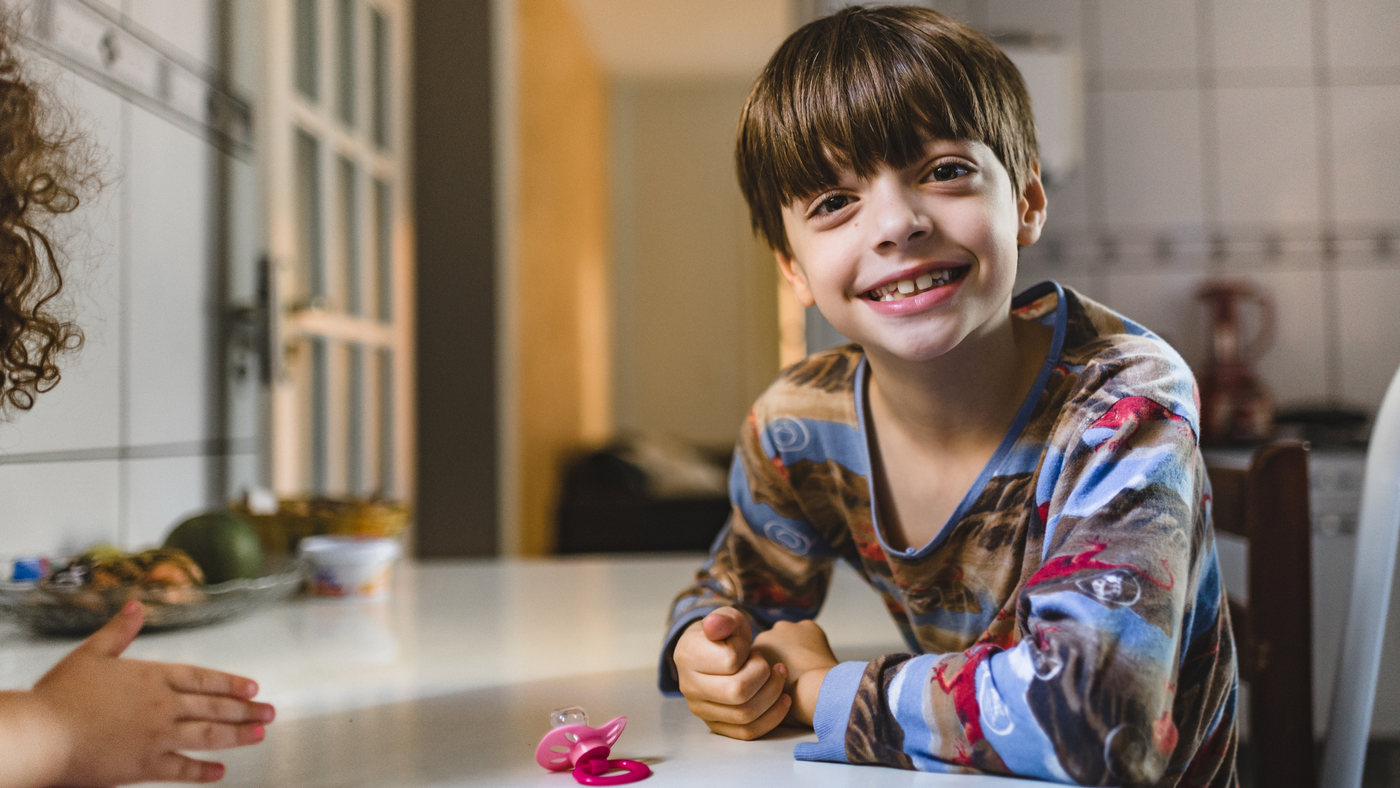 little boy wearing pyjama set sitting at dining table in kitchen