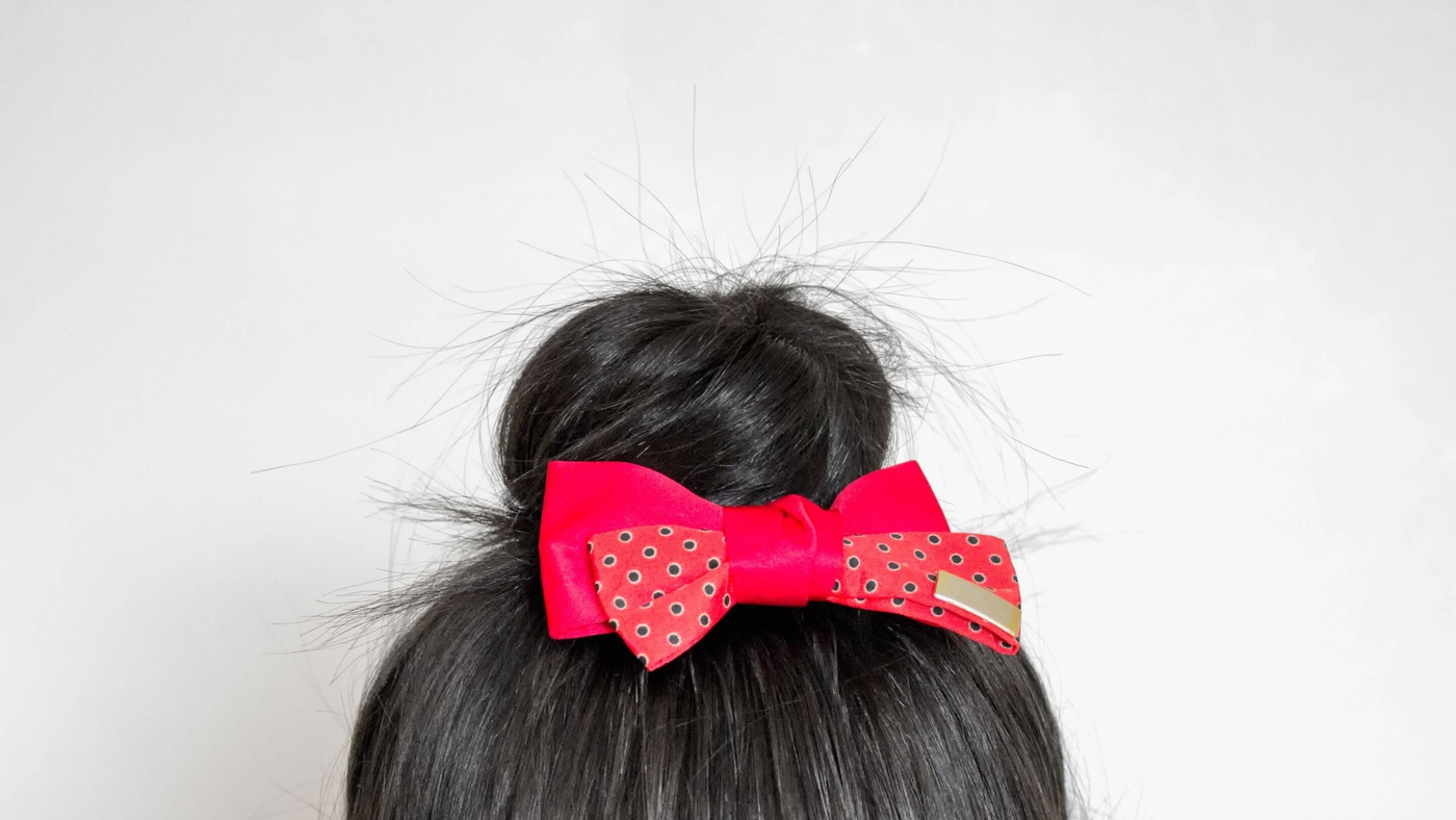hair bun finished with a red polka dot bow