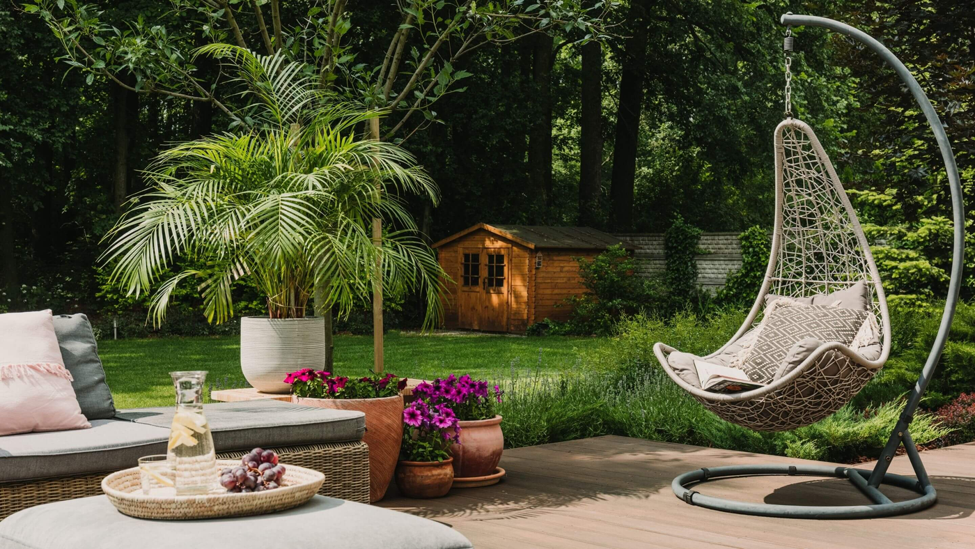 basket egg chair in garden space with shed and large fern plant in the background