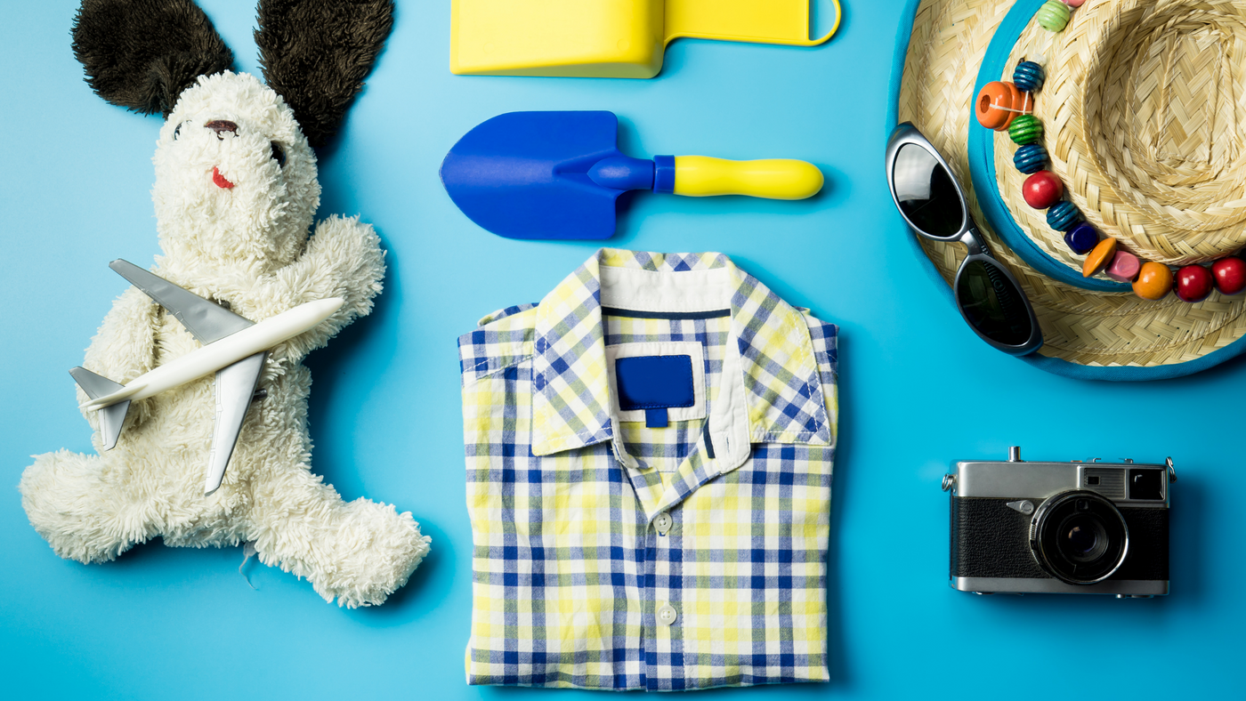blue background with boys shirt, summer hat, sunglasses and teddy bear