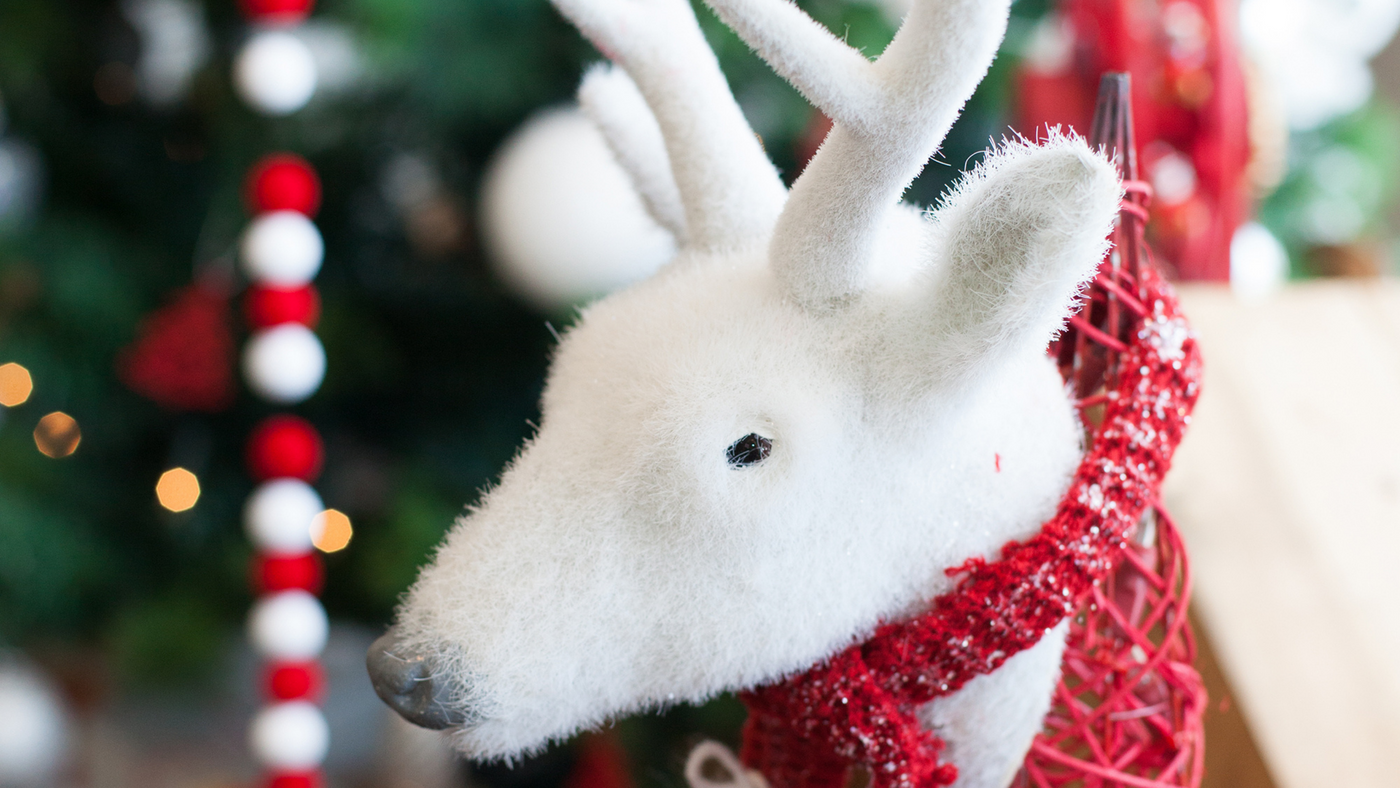 white reindeer decoration with christmas tree in the background