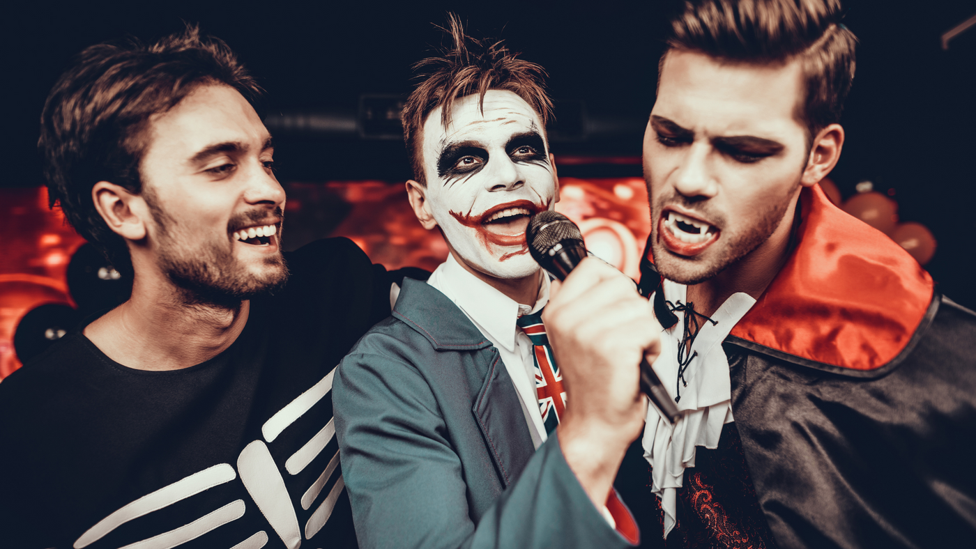three men on halloween doing karaoke dressed as a skeleton, the joker and a vampire