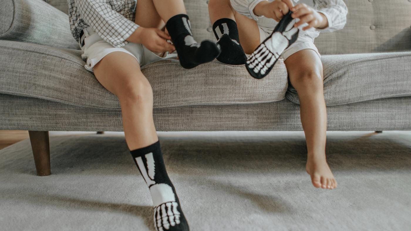 two little boys on the sofa putting on skeleton style socks