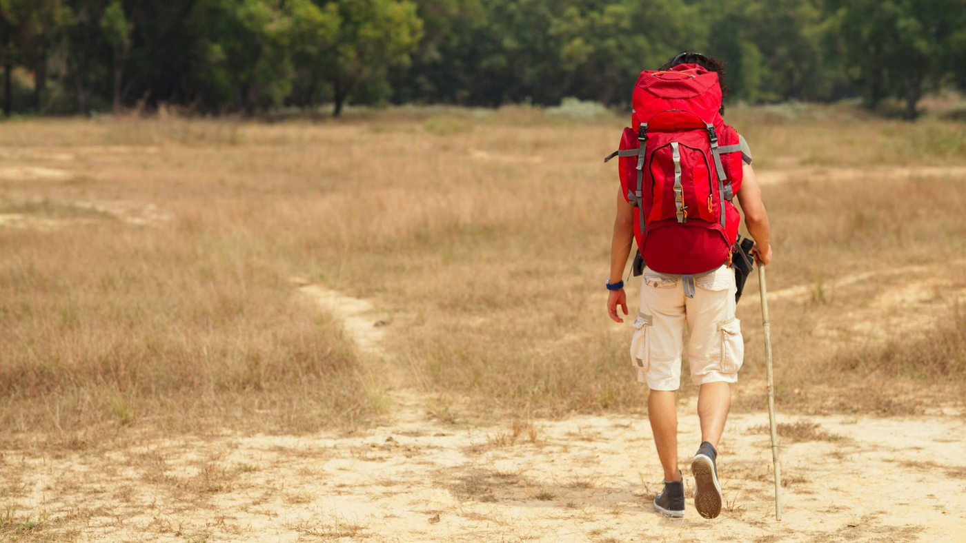 person hiking in desert like location wearing red trekking rucksack