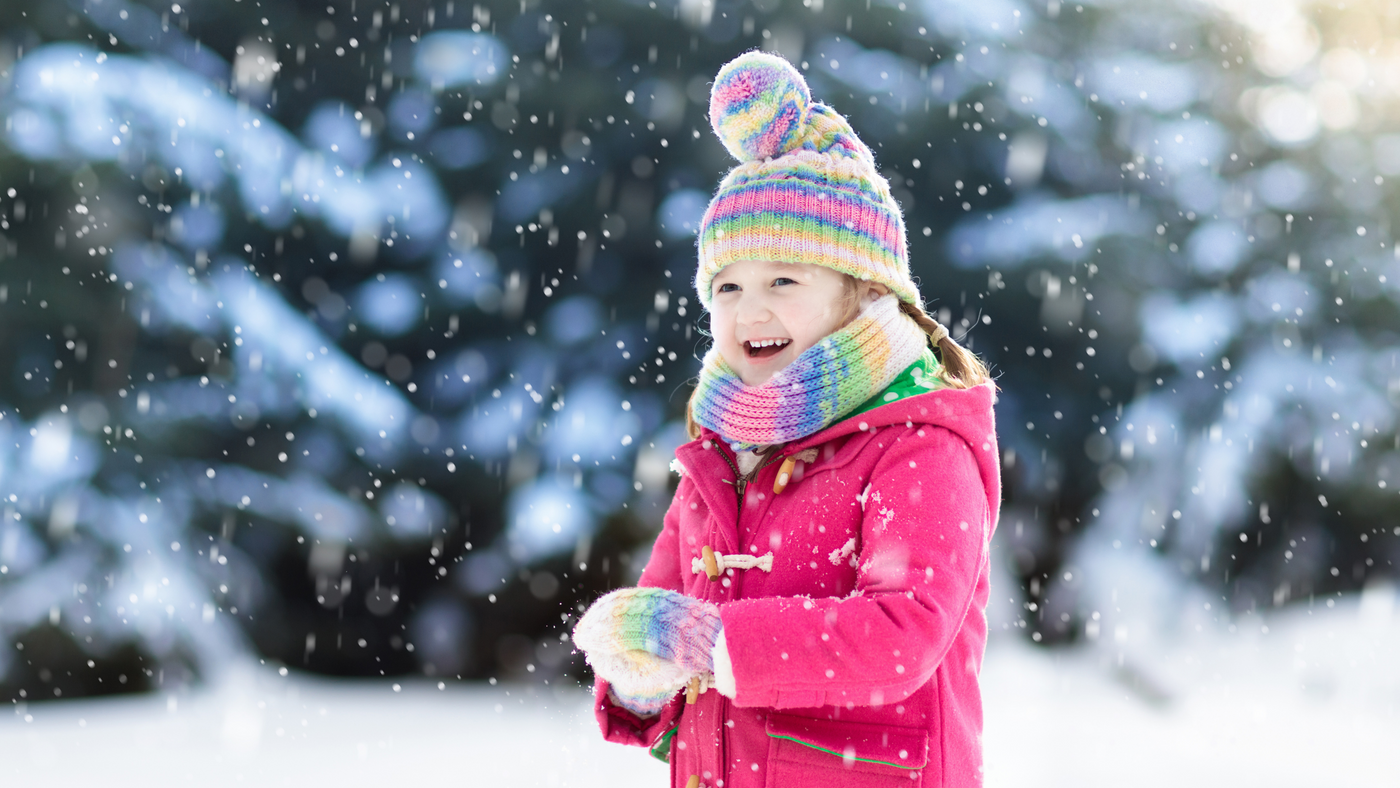 little girl playing in snow wearing pink jacket and multi colour hat scarf and glove set