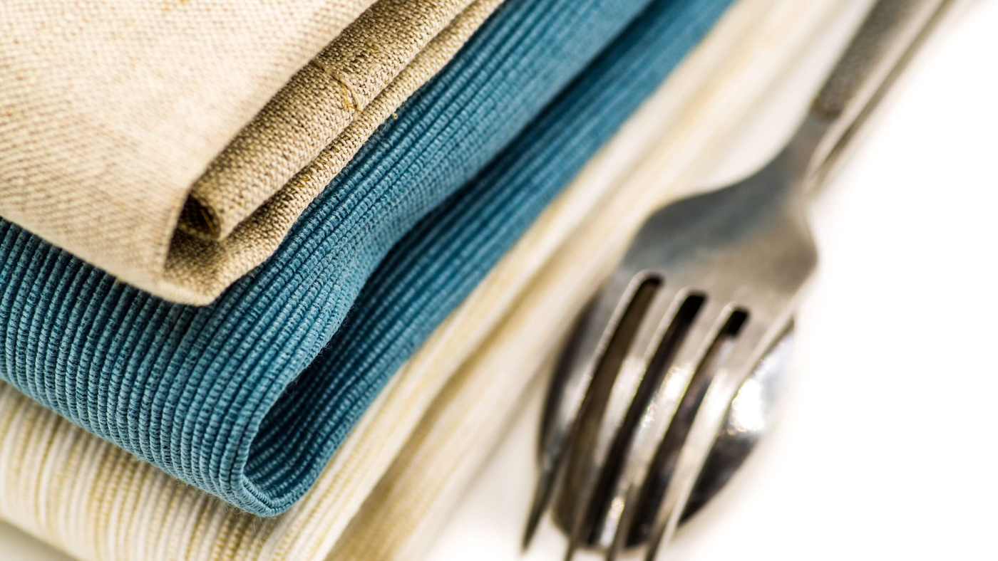 blue and ivory table linen beside silver fork and spoon