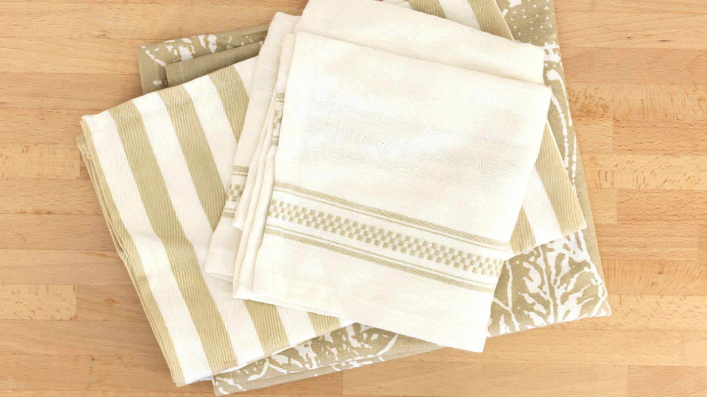 ivory and gold tea towel set on wooden counter top