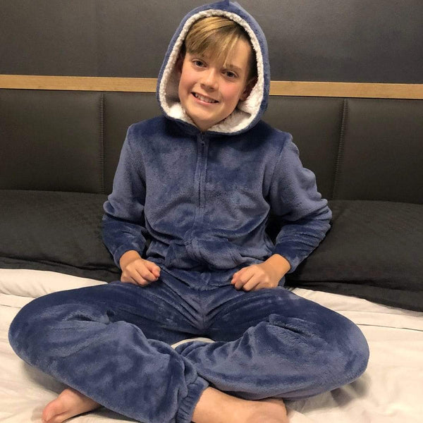 boy sitting on bed wearing a blue onesie pyjama suit