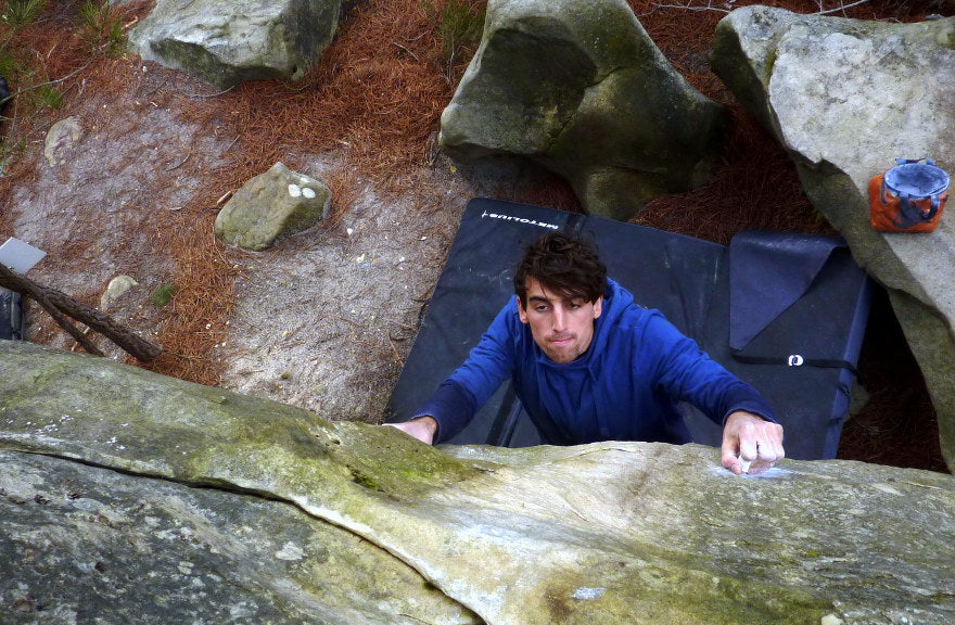 boulderer going for the top in fontainebleau