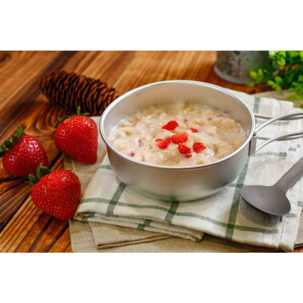 Expedition Foods Porridge with Strawberries shown in a bowl, next to a spoon and fresh ingredients