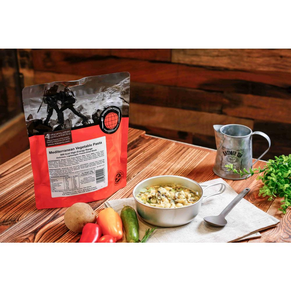 Expedition Foods Mediterranean Vegetable Pasta pack, shown on table next to food in bowl