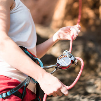 Wild Country REVO belay device, shown in use with a climber in the outdoors
