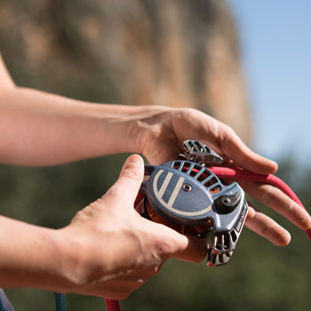 close up of the Wild Country REVO shown in use with a climber outdoors, with a red rope