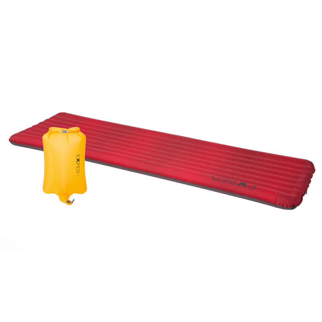 Exped SynMat UL Winter LW sleeping mat, shown laid out in red colour with yellow pump sack