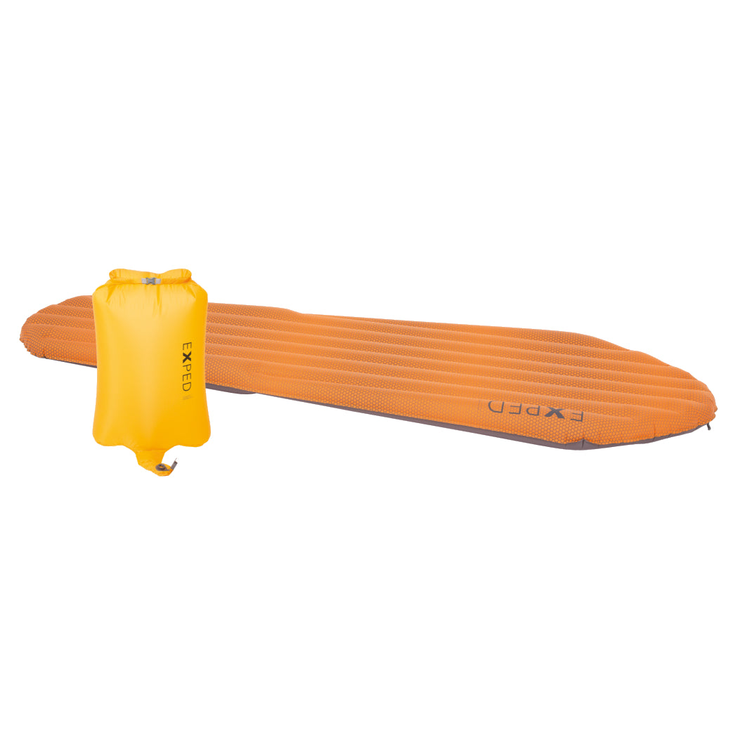 Exped SynMat HL LW sleeping mat, shown laid flat in Orange colour next to yellow pump sack