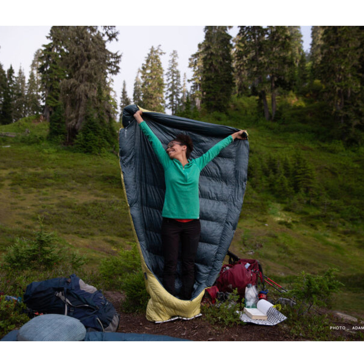 Thermarest Corus 20F/-6C Quilt in golden colour showing person holding it in air