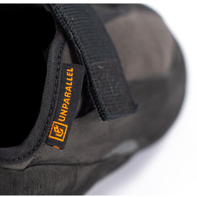 Unparallel logo in orange on a black tab with rest of shoe blurred out in background